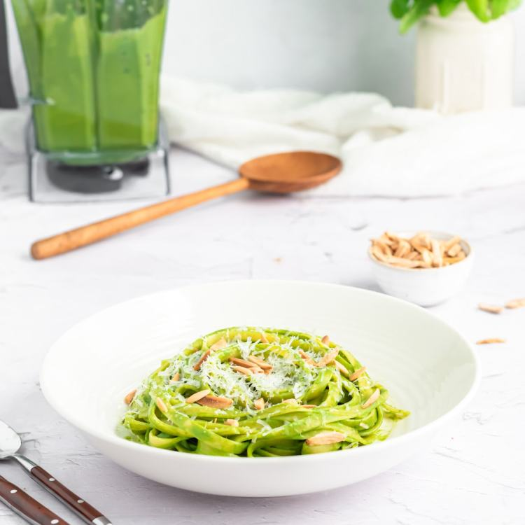 a close up of green spaghetti sauce coated pasta in a shallow white bowl topped with parmesan cheese and slivered almonds