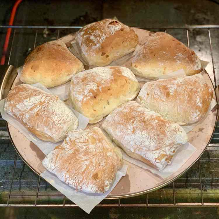eight fully baked, golden brown roasted garlic and fennel olive oil ciabatta rolls are arranged on individual pieces of parchment paper on top of a baking stone. The baking stone is on an oven rack which has been pulled halfway out of the oven.