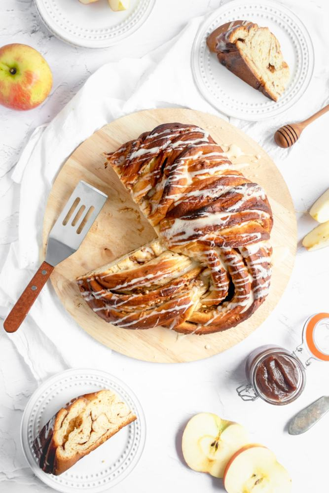 An overhead shot showing an apples and honey babka drizzled with honey icing on a wire cooling rack on a marble countertop. Above the rack are two halves of a small apple. To the right of the apple is a small dessert plate with a zig-zag border and two wedges of babka. One wedge is turned on its side revealing all the swirls and layers inside.