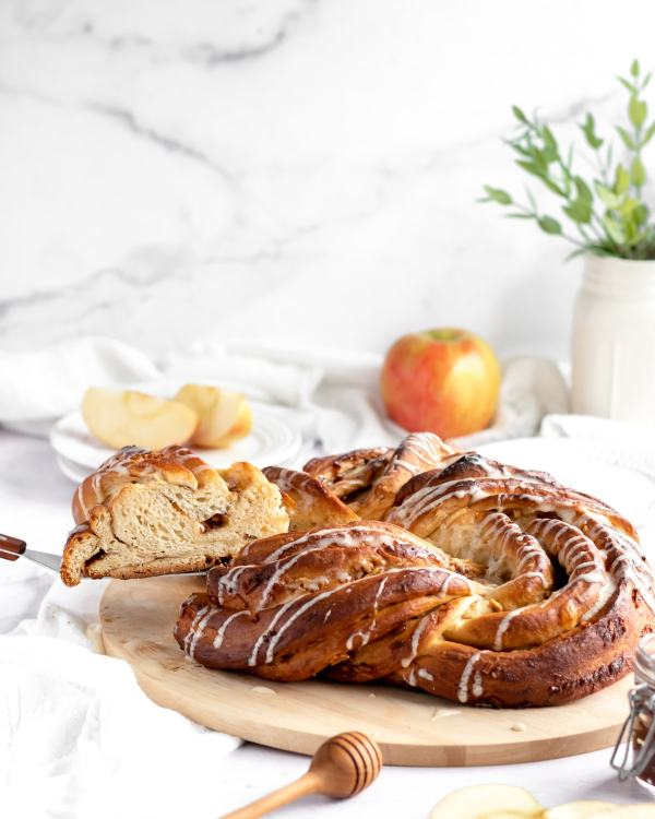 An apples and honey babka drizzled with honey icing sits on a wire cooling rack on a marble countertop. A small red and yellow apple sits in the background.