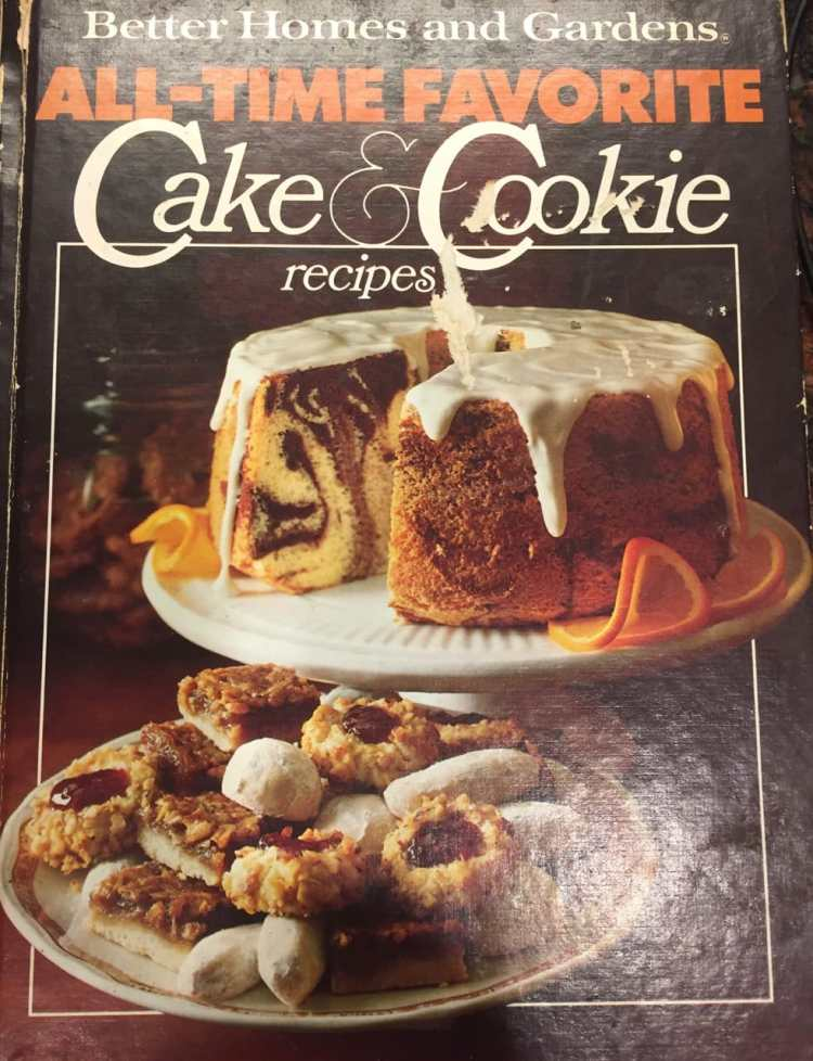 The cover of the Better Homes and Gardens All-Time Favorite Cake & Cookie Recipes book that my dad found the Chocolate Revel Bar recipe in. The cover has the title across the top and a black-and-white marbled angel food cake with white icing dripping down the sides on the cover. The cake is on a cake stand, and below it is an assortment of cookies on a plate.