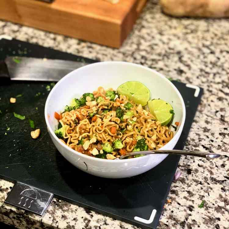 A white bowl filled with Malaysian Ramen, a one-skillet dinner, sits on a dark grey cutting board. In the bowl are curly yellow ramen noodles, tiny pieces of broccoli and carrots, and two lime wedges.