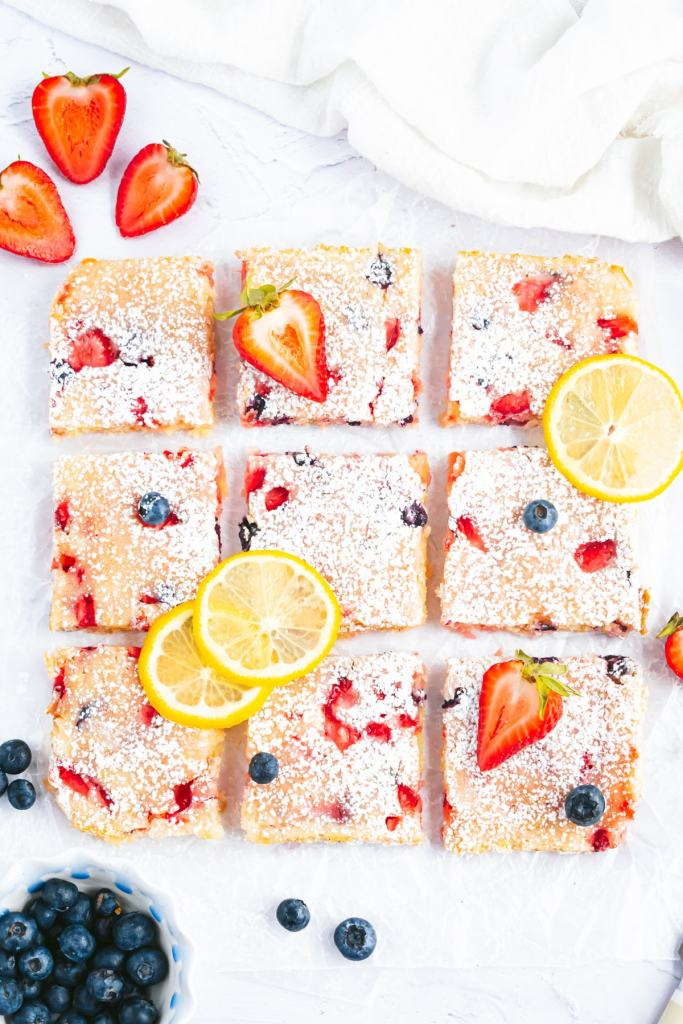 an overhead shot of 9 lemon berry blondies arranged in a 3 by 3 grid with a small amount of space between them. below the blondies is a small bowl filled with frozen blackberries and strawberries.