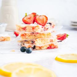 Four lemon berry blondies in a stack with other berries and lemon slices nearby