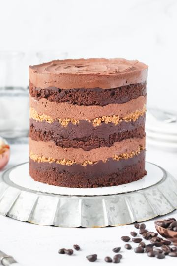 a mocha hazelnut layer cake on an overturned metal fluted plate