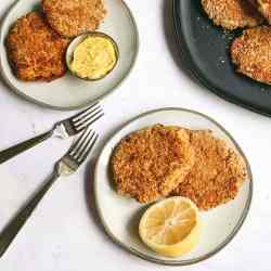 an overhead shot of two tuna cakes on a small grey plate with half of a whole lemon. two additional plates with more tuna cakes are on the table above it. one of them has a small bowl of aioli on it.