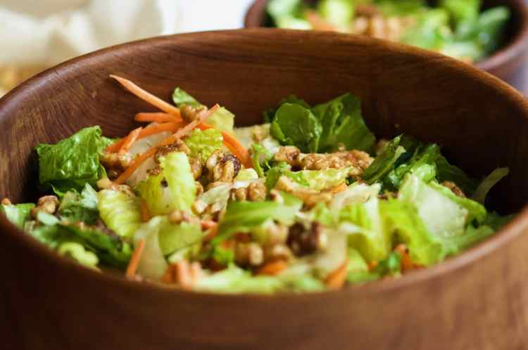 A tight shot of a wide wooden salad serving bowl with straight sides. The bowl is filled with bright green romaine lettuce, slivered carrots, and walnuts. Blurry in the top right corner of the frame is a small salad bowl filled with more lettuce and walnut salad.
