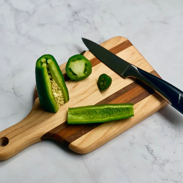 On a small wooden cutting board a jalapeno stands vertically. The stem end and tip have been removed, and the wider end is flat against the cutting board. One side of the pepper has been removed cleanly between two visible ribs. Inside the pepper seeds are crowding the opening. A small paring knife sits on the right end of the cutting board.