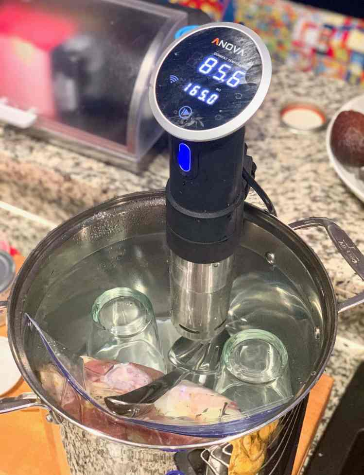 The sous vide carnitas cooking process: A sous vide is attached to the side of a large metal stock pot. A bag filled with pork is submerged in the water. Two upside down pint classes and a large metal serving spoon are helping weigh down the bag.