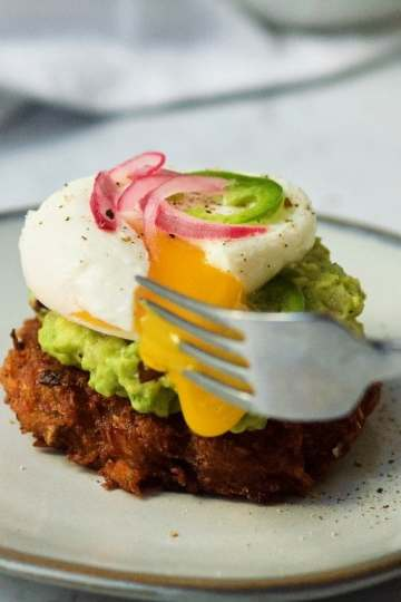 a fork pierces through the side of a poached egg perched on top of guacamole on a small potato pancake