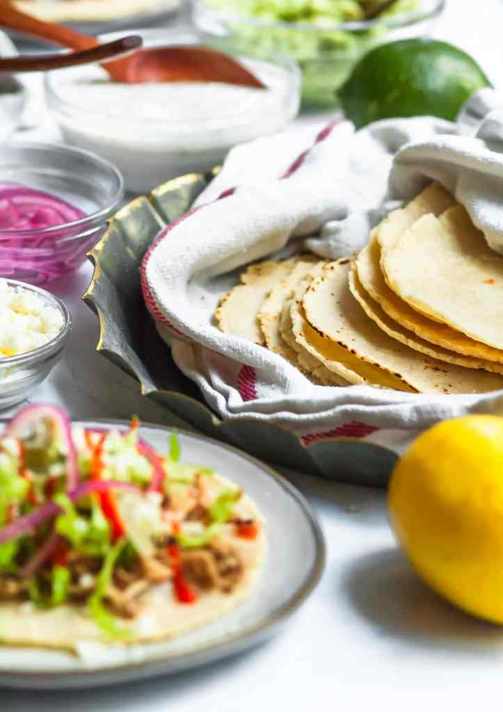 A close up of a taco bar with all the toppings on a counter. A pile of homemade corn tortillas wrapped in a dish towel is in the center, in focus. Everything else is out of focus around it, including an assembled taco in the foreground.