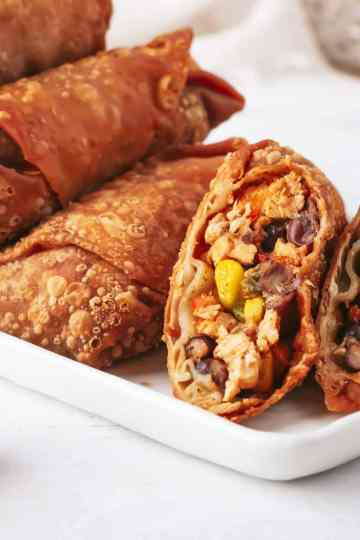 egg rolls on a white rectangular plate. at the end of the plate is an egg roll that's been split in half diagonally with both halves facing forward so you can see the filling. lime wedges are on the table around the platter.