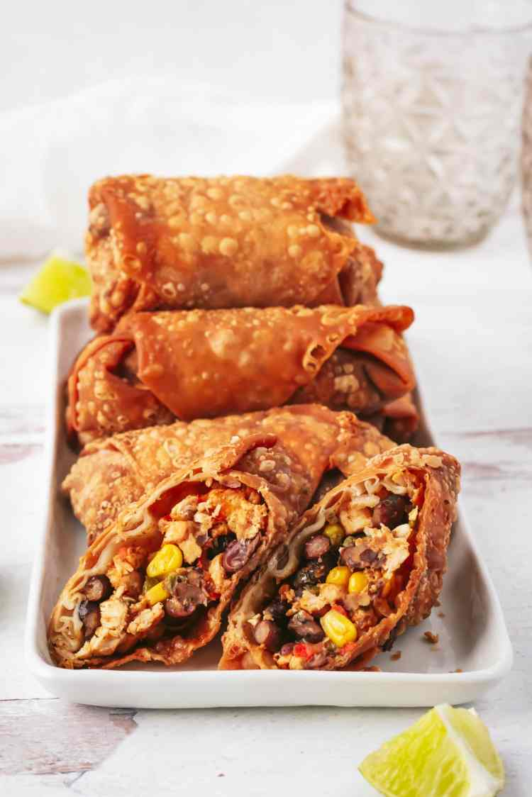 a straight on shot of a platter of southwest egg rolls stacked on top of each other. in the front of the platter is an egg roll sliced in half diagonally to reveal the filling inside.