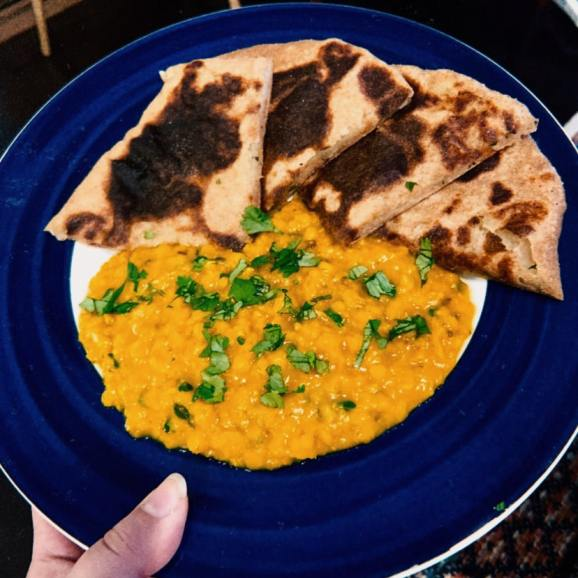 One aloo paratha cut into quarters and arranged on a plate with a serving of dal. Both are good emergency recipes because they use a lot of shelf stable dry goods.