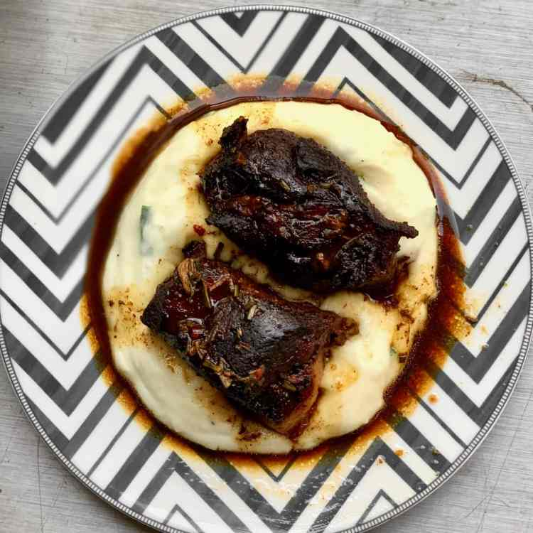 an overhead shot of two pieces of pork agrodolce on a pile of creamy mashed potatoes