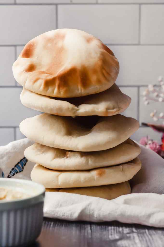 A vertical stack of six golden brown pita breads.