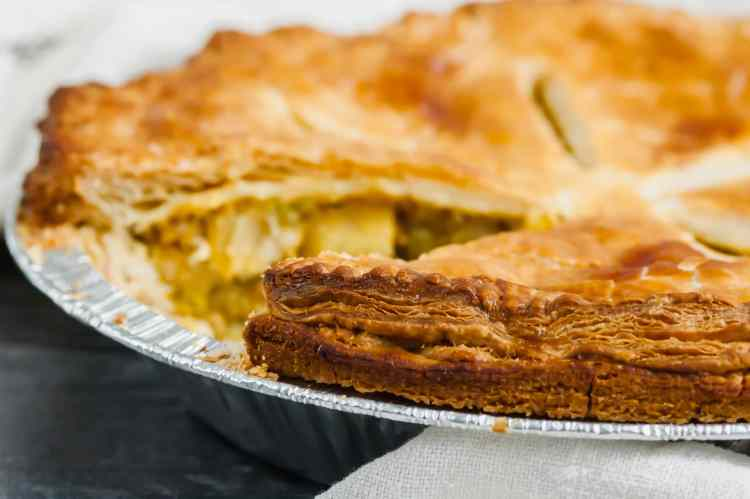 A side angle view of a samosa pot pie with one slice cut out. the filling is out of focus but the crispy flaky layers of the outside edge of the puff pastry are in focus in the foreground.