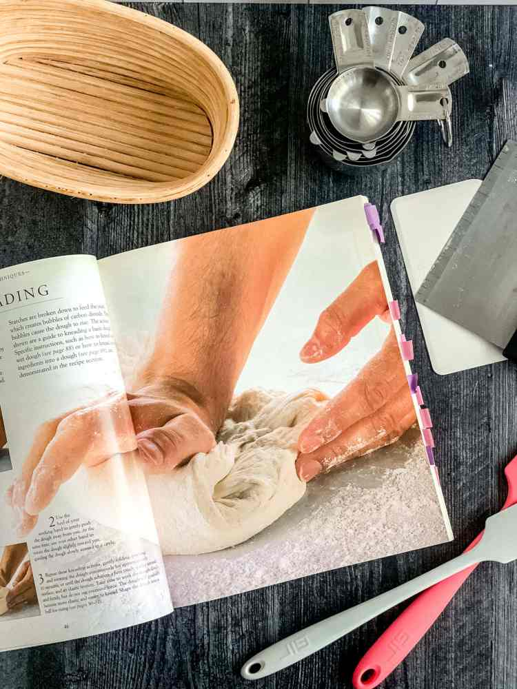 The book Bread is open to page 47, showing a large image of two hands kneading a folded piece of dough against a lightly floured countertop.
