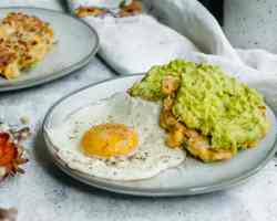 two corn fritters topped with mashed avocado on a small plate with a fried egg. in the backgroud another plate with corn fritters on it is visible.