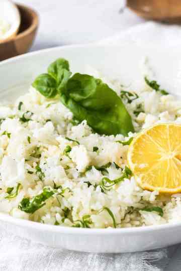 a close up of a bowl of rice topped with basil, lemon, and feta
