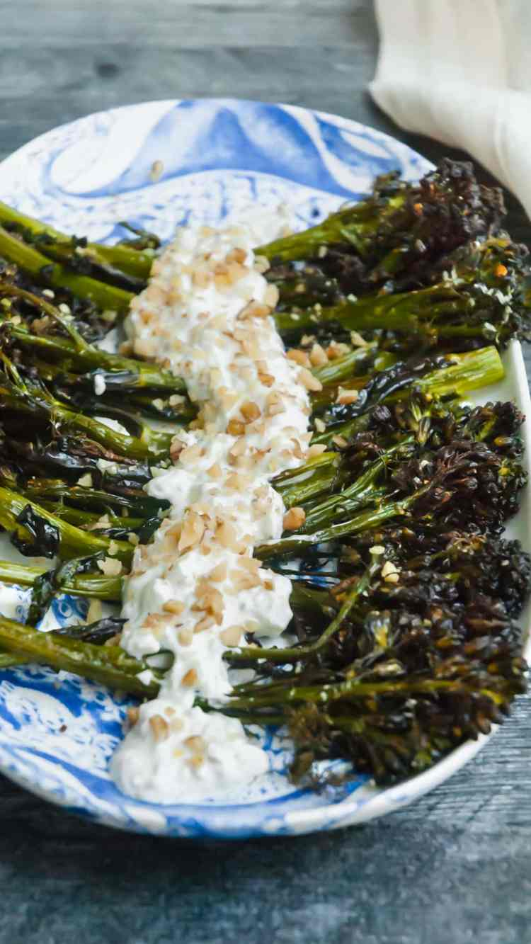 roasted broccolini on an oval platter with a yogurt walnut sauce drizzled across the stems