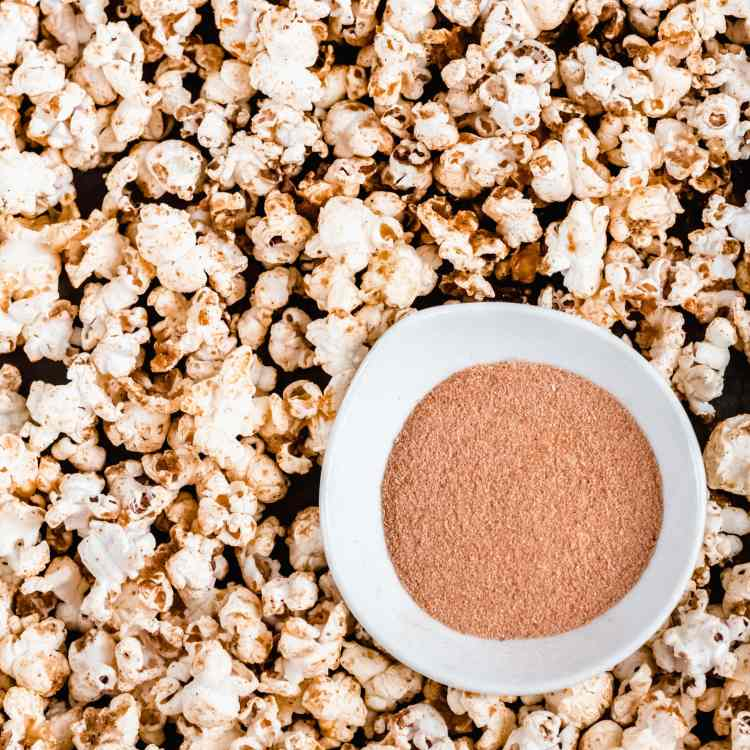 a close up overhead shot of chex mix popcorn. a small white bowl with seasoning powder rests on top of it.