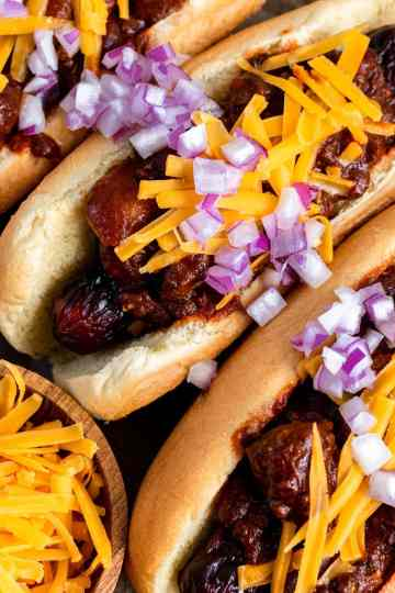 an overhead close up shot of three chili dogs next to each other. a small bowl of shredded cheddar is next to them.