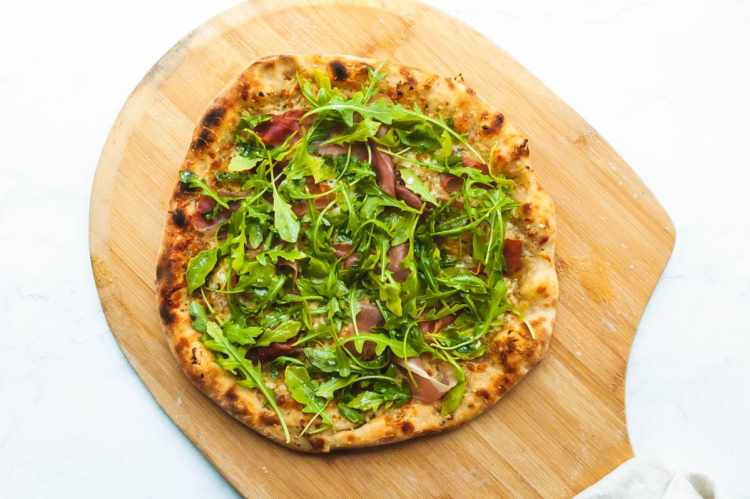 an overhead shot of a pizza topped with arugula and prosciutto on a wooden pizza peel