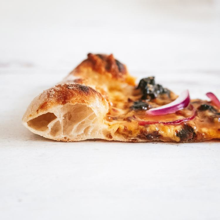 a close up side shot of a perfect slice of pizza cooked on a baking steel, showing the bubbly, airy crust