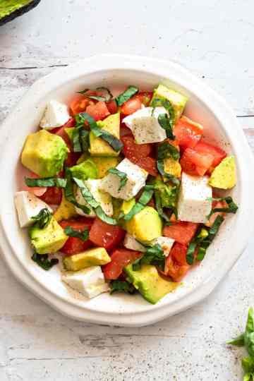 an overhead shot of chopped caprese salad on a white plate. on the distressed white wood table around it are two slices of tomato, a bunch of fresh basil, a small bowl of salt, and two empty avocado skins.