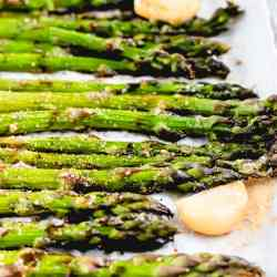 a close up of roasted asparagus on a sheet pan with garlic cloves
