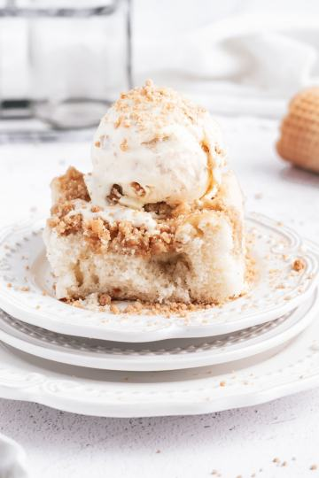 a scoop of crumb cake ice cream on top of a square of crumb cake