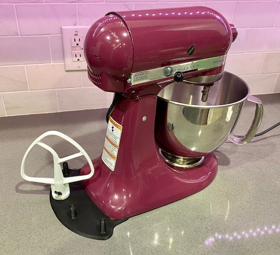 a purple mixer with a black flat base behind it. the base has four pegs on it to hold the mixing attachments.