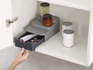 a light grey plastic three tier organizer with a dark grey drawer