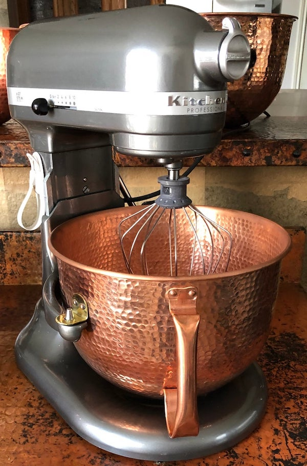 a kitchenaid bowl-lift mixer with a hammered copper bowl in it