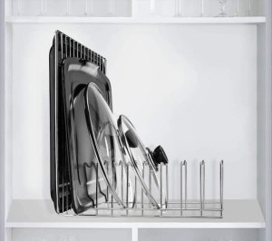 a wire metal rack holding cutting boards, sheet pans, and pot lids vertically in a cupboard