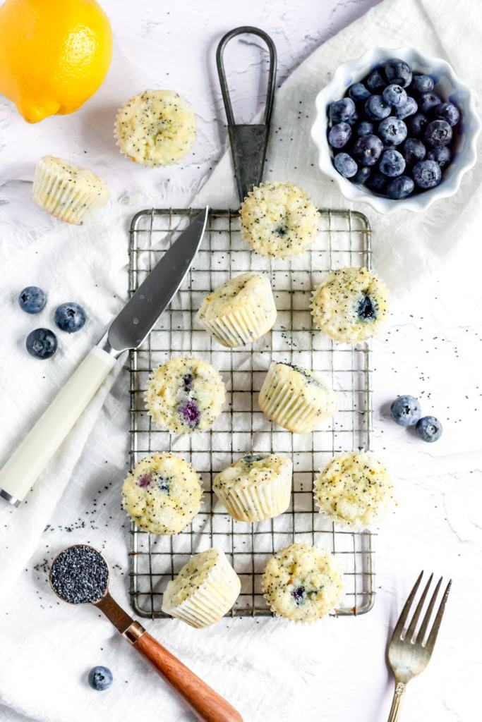 an overhead shot of mini muffins on a cooling rack with poppyseeds, fresh blueberries, and a lemon nearby