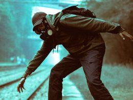 man in gas mask crossing train tracks
