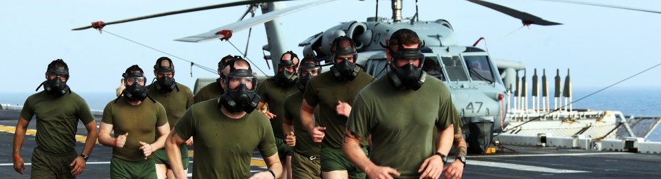 Men running in CBRN gas masks