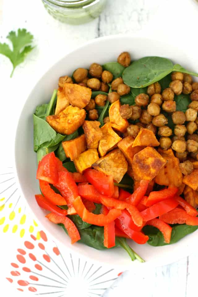 A healthy and filling salad with roasted sweet potatoes, chickpeas, red pepper, and spinach, all topped with a cilantro vinaigrette. Healthy and so tasty! Vegan and gluten free.