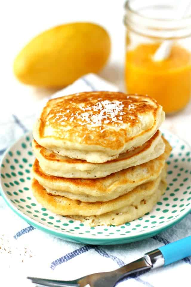 Light and fluffy vegan coconut pancakes are topped with a sauce made from fresh mangoes. A delicious breakfast treat!