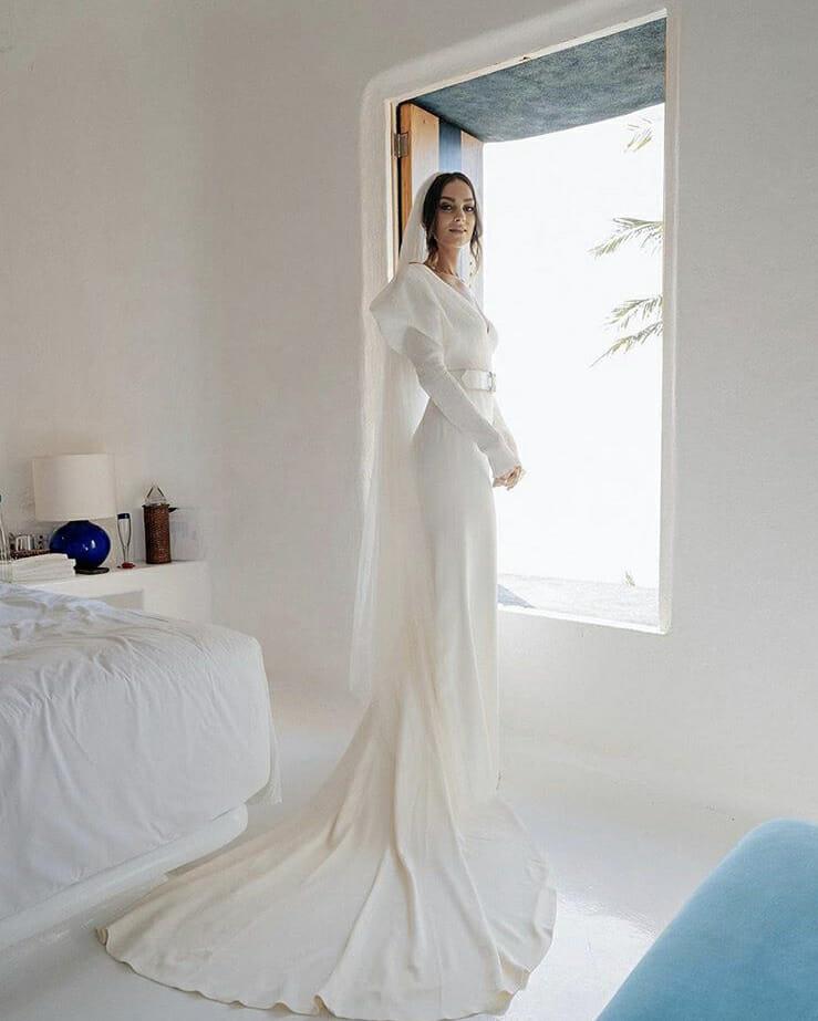 Woman in wedding dress posing in front of an open window