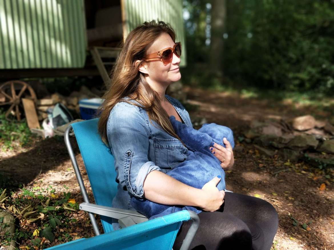 A woman is sat outside on a deck chair. She is wearing sunglasses and a denim shirt. She is breastfeeding her baby