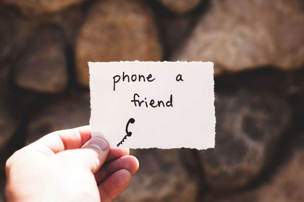 Someone holding a piece of paper with Phone a friend written on it with a picture of a phone