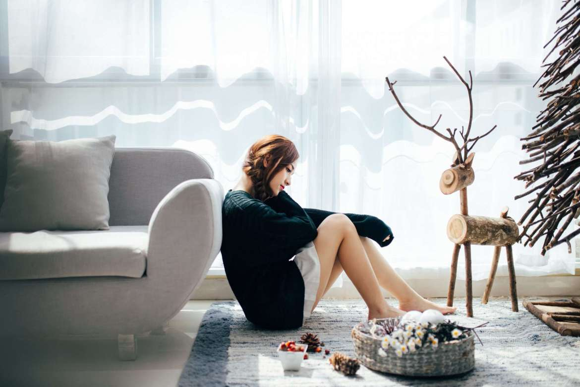 A woman in a green jumper is sat on the floor, leaning up against a cream/grey sofa. She looks sad. There is a large reindeer made out of logs near her, a Christmas tree and decorations on the floor