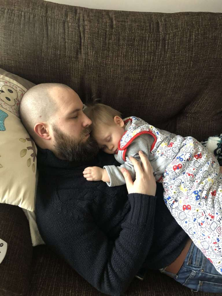 Darren laying on the sofa with Little J laying on him. They are both asleep