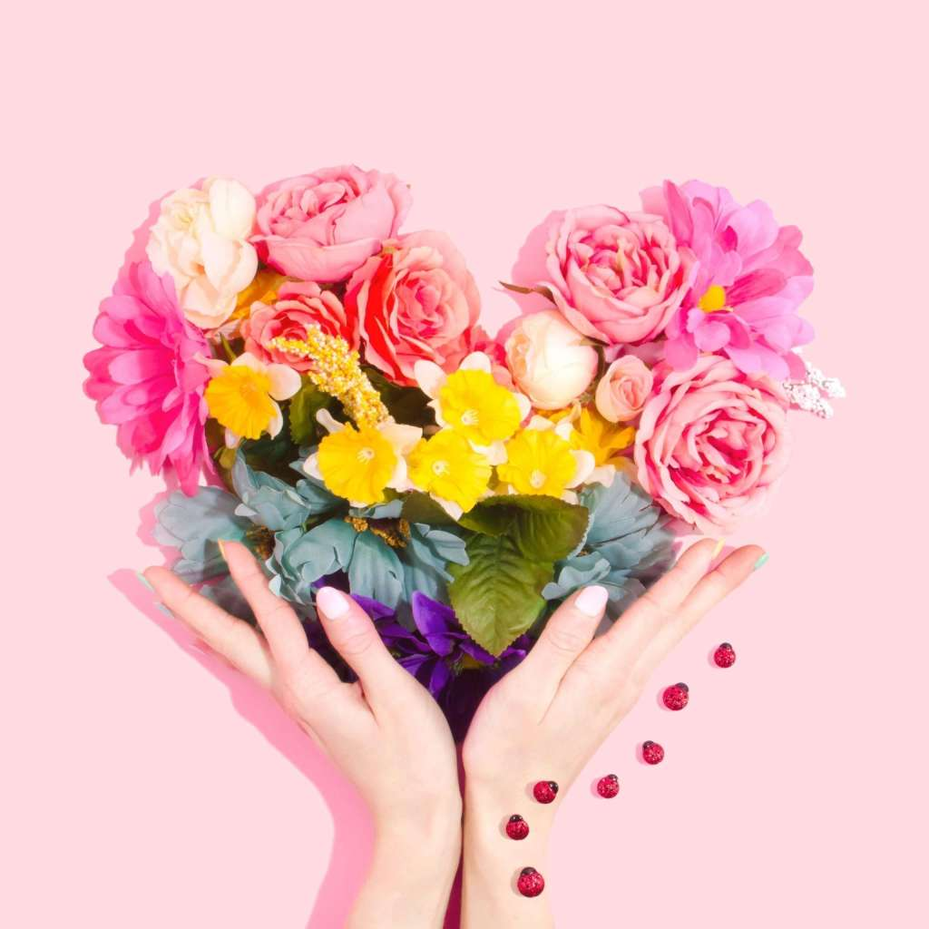 An assortment of flowers in a heart shape being held up by a pair of hands against a pink background