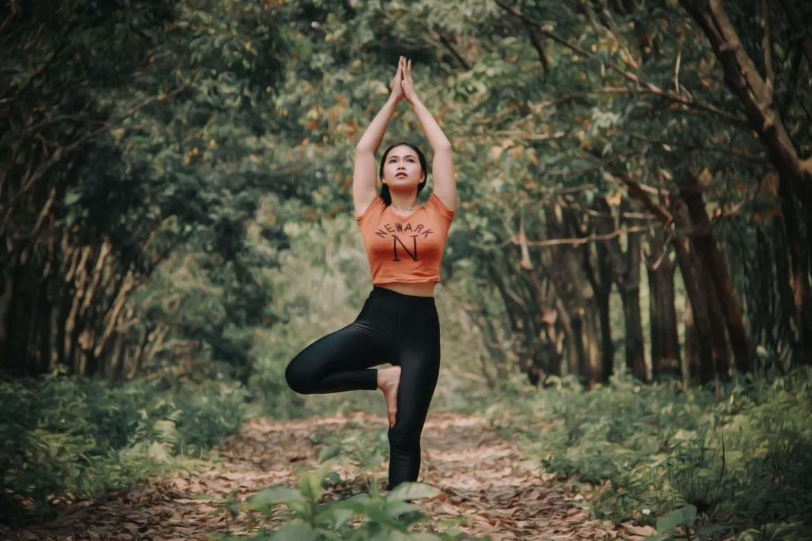 A woman in an orange top and black leggings is barefoot in the forest with her arms up in a yoga position