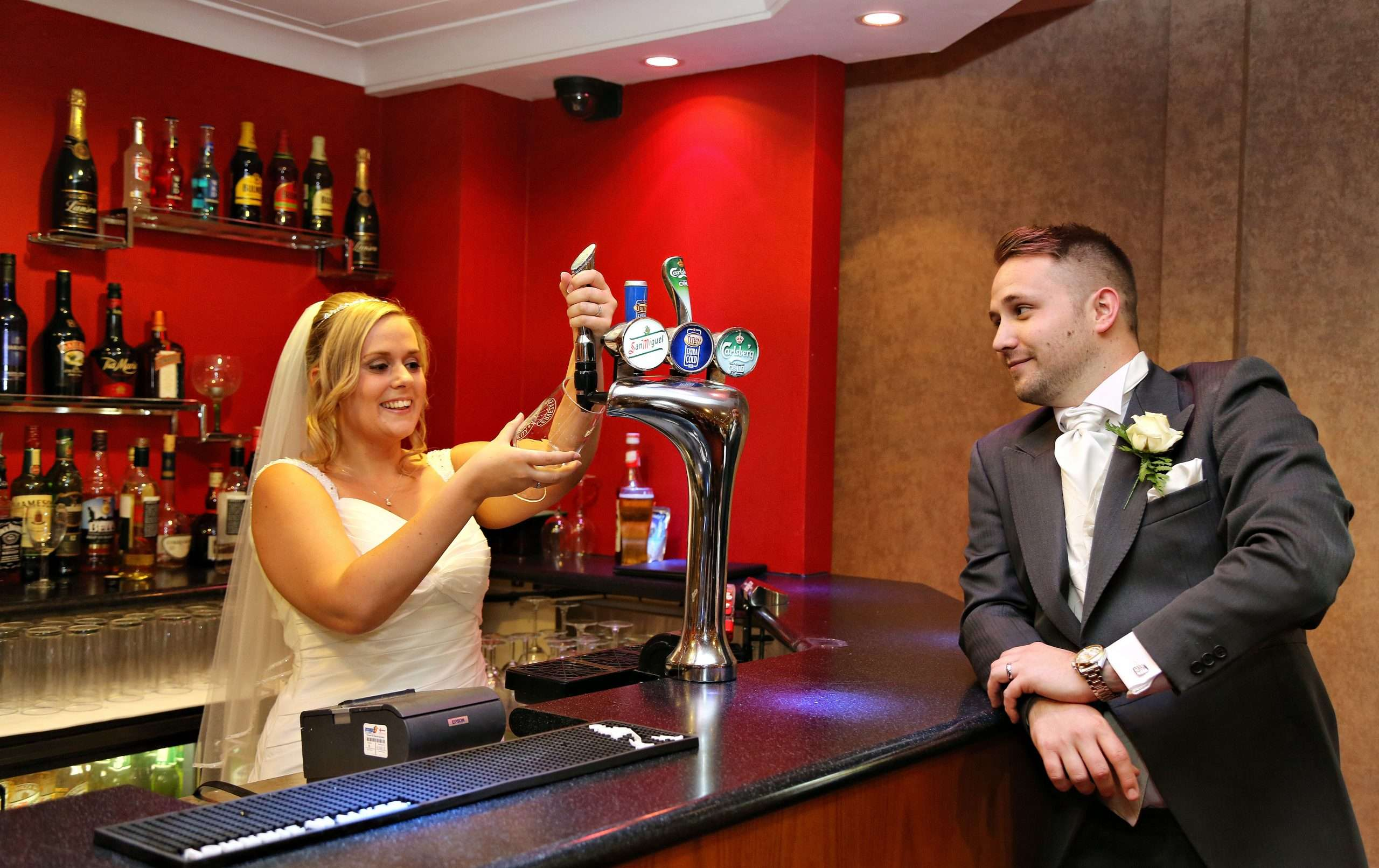 Lisa and Darren in their wedding outfits. Lisa is pretending to pour Darren a beer from the pump