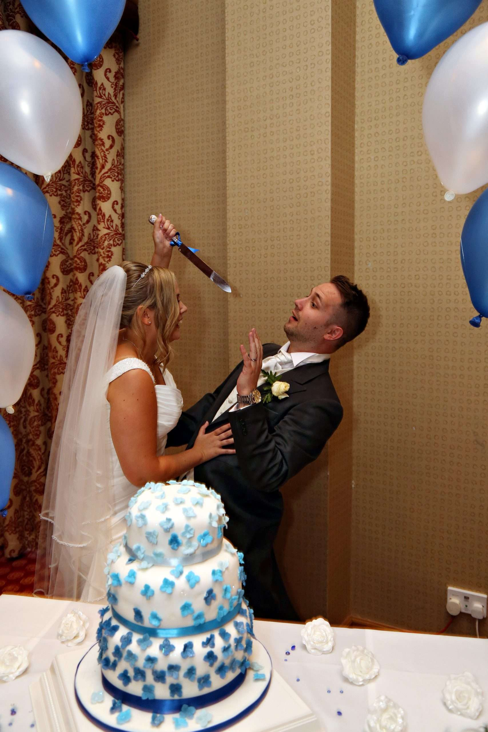 Lisa trying to stab Daz with the cake knife on our wedding day. A white and blue wedding cake is in front of us and we are under a blue and white balloon arch